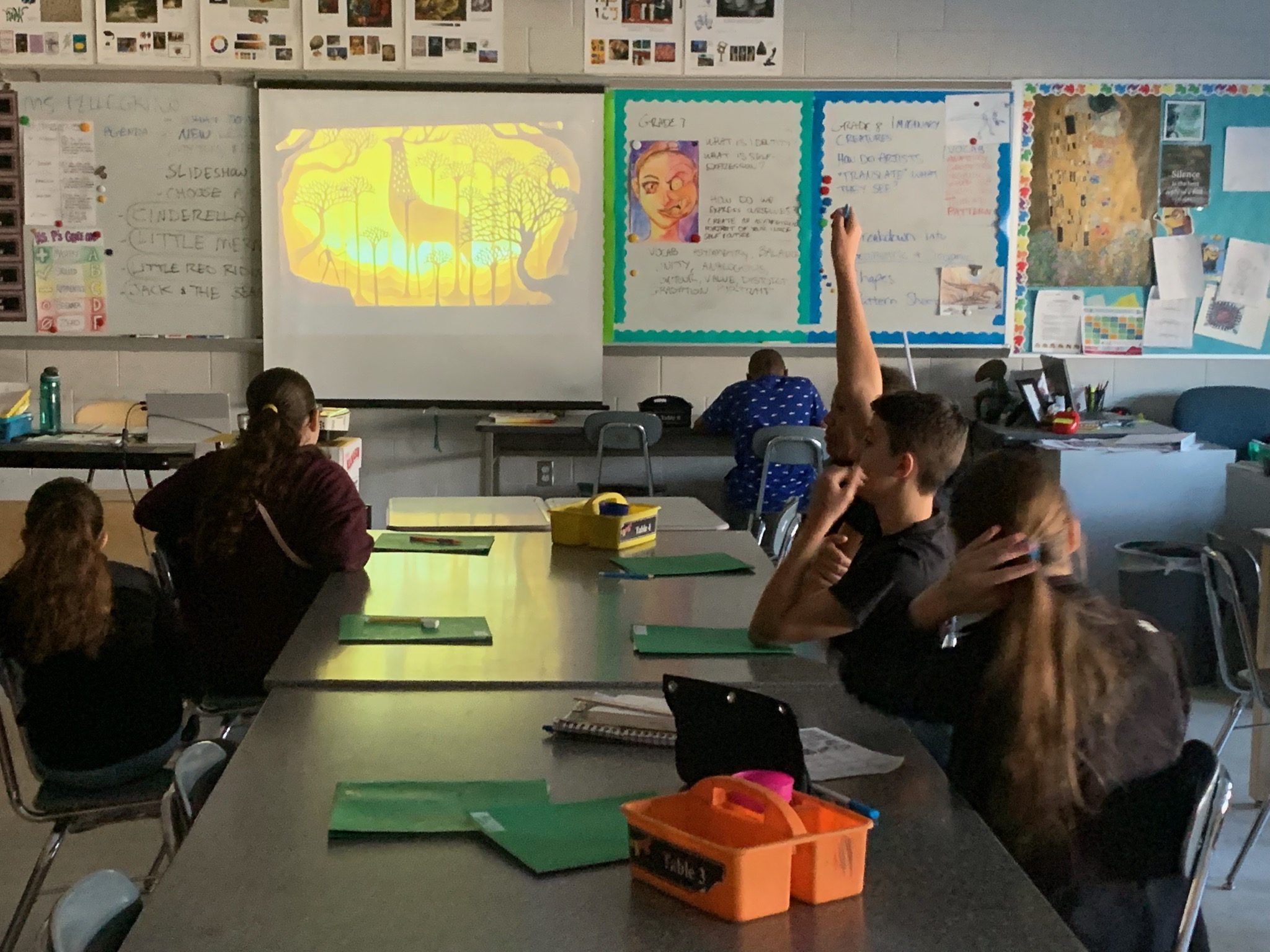 Students respond to prompts and questions during a lesson's introductory slideshow presentation.